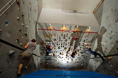 Students climb on the climbing wall at The Rock