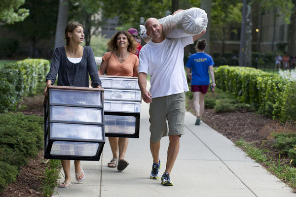 Parents help their daughter move into her residence hall