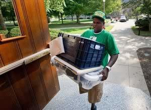 A student wearing a green Notre Dame hat and shirt carrying items into a building