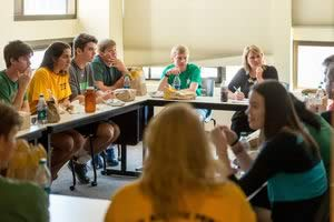 Twelve students seated around tables having a discussion