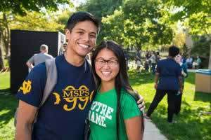 A young couple wearing Notre Dame t-shirts outside