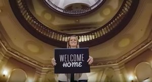 A young woman holding a blue sign saying Welcome Home